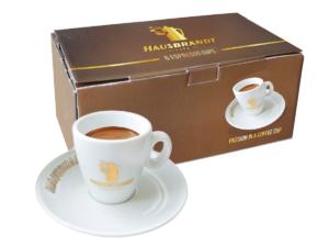 Hausbrandt espreso šoljice za kafu. Porcelanska šoljica debelog dna i zidova koja zadržava toplotu espresa i njegove karakteristike do konzumacije. Bele šoljice odišu elegancijom i ističu braon tonove kafe.